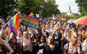 a group of people posing for a picture while holding an umbrella: People hold flags and placards during the first gay pride march on July 20, 2019 in the city of Bialystok, in eastern Poland - Photo by Jerzy Baliski / AFP/Photo by Jerzy Baliski / AFP