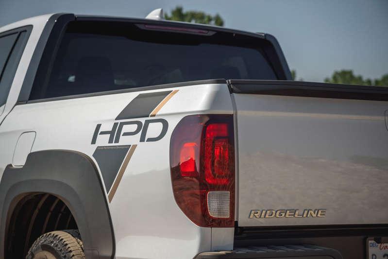 a truck is parked in front of a car: 2021 Honda Ridgeline Sport HPD