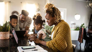 Black family, mother working from home holding toddler-age daughter, with husband and son in background