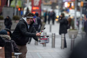 A person wearing a mask and face shield uses a clapboard during the filming of a TV series in Times Square this past March. Alexi Rosenfeld/Getty Images