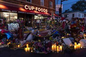 Candles flowers and signs are seen outside the Cup Foods in Minneapolis where George Floyd was killed during a candlelight vigil at George Floyd Memorial Square on Tuesday, May 25, 2021.