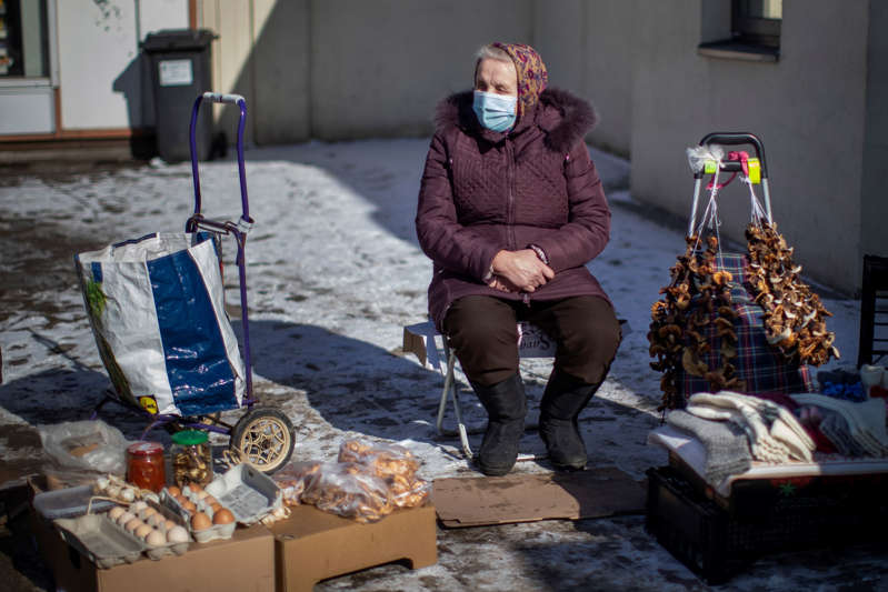 A woman wearing a face mask to protect against coronavirus, sells mushrooms, eggs and socks on the sidewalk in Vilnius, Lithuania, Tuesday, March 9, 2021. (AP Photo/Mindaugas Kulbis)