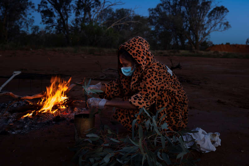 Patricia Wilson gathers eucalyptus leaves and other plants that she burned in a metal tin in an effort to ward off covid-19 at the Warrawong campground in Wilcannia, Aug. 30.
