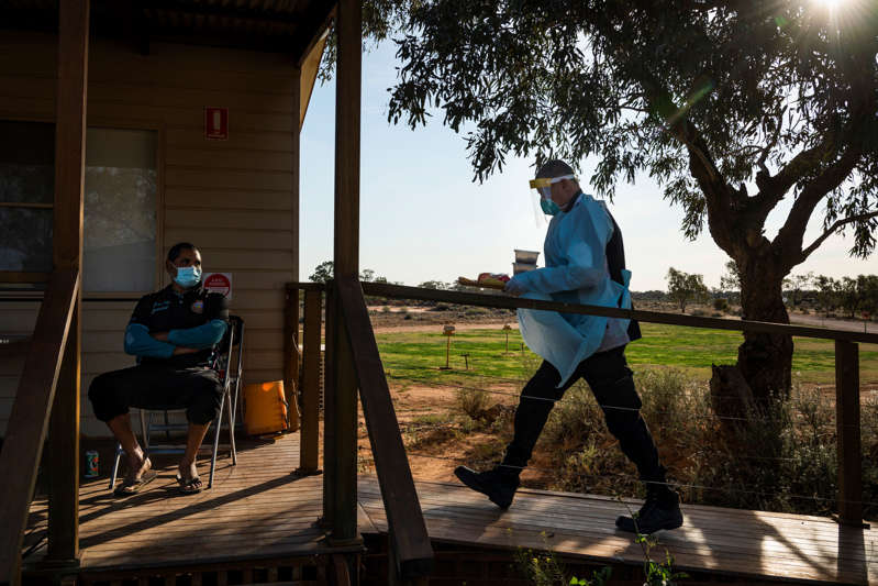 A security guard from Wilcannia Hospital delivers food to the occupants of a makeshift quarantine facility at a campground on Aug. 30. Anthony Dutton, left, and his family had to walk to the campground.