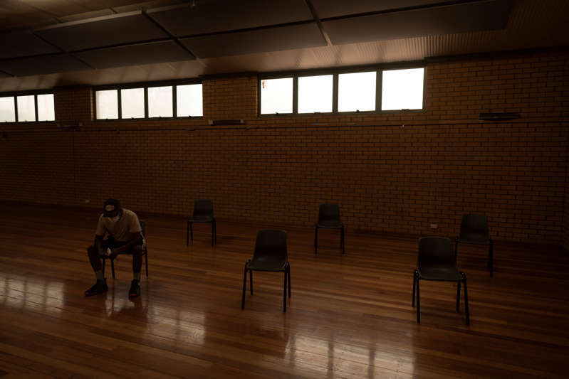 Anthony Elwood, 24, sits in Wilcannia's town hall, which is now the waiting room for the monitoring of people who have just received their coronavirus vaccinations. The Aboriginal farm worker traveled to the town to receive his first shot on Sept. 3.