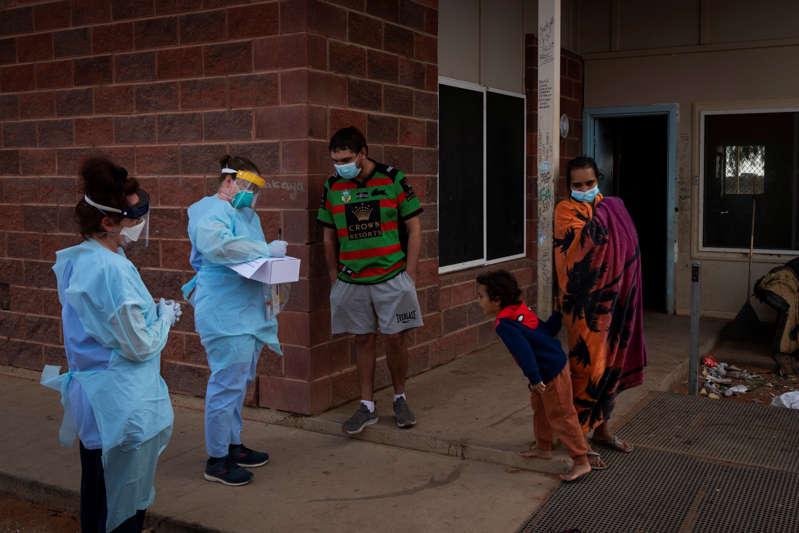 A family of 13 wait to be tested for the coronavirus by a mobile New South Wales Health team. The tests all came back positive.