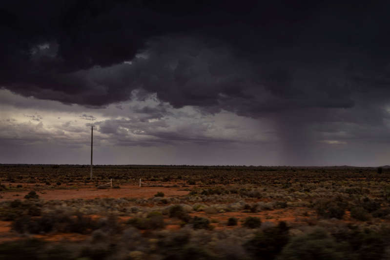 An afternoon storm rolls in, kicking up dust across the dry landscape between Wilcannia and Broken Hill, Australia.
