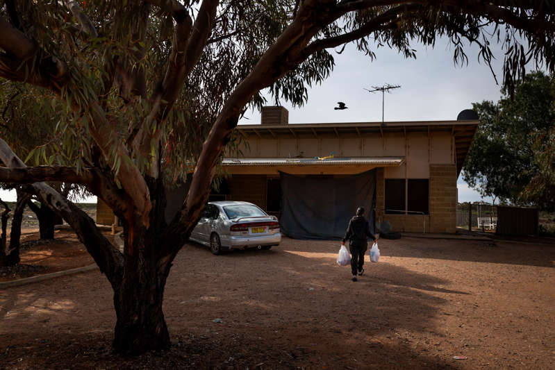 Saphire Hall's relative, who was in home quarantine, picks up some groceries in her front yard, Aug. 30. Locals had long feared what would happen if the virus found its way to Wilcannia.