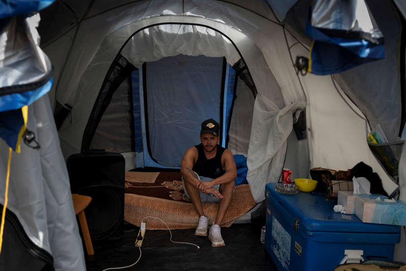 Allan Whyman sits inside a tent, away from other family members.