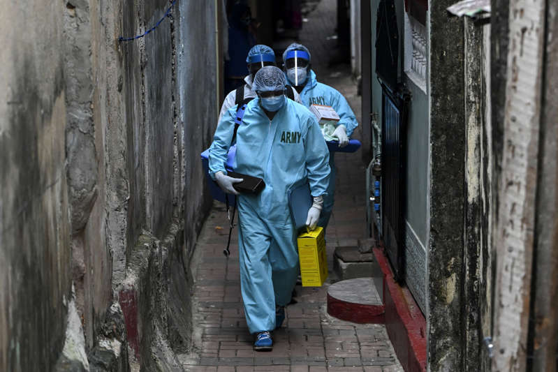 Army health officials walk through an alley during the Covid-19 coronavirus mobile vaccination drive for residents of a locality in Colombo on August 12, 2021. (Photo by Ishara S. KODIKARA / AFP) (Photo by ISHARA S. KODIKARA/AFP via Getty Images)
