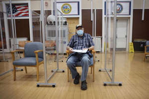Army veteran William Craig waits to see if he has a reaction after receiving a COVID-19 booster vaccine and flu shot at Edward Hines Jr. VA Hospital on September 24, 2021, in Hines, in Illinois.