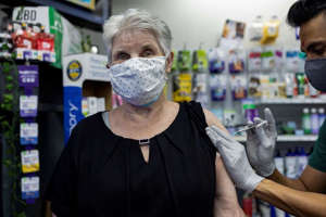 A woman receives the Pfizer-BioNTech coronavirus disease vaccine (COVID-19) as a booster dose at the Skippack Pharmacy in Schwenksville, Pa. On August 14, 2021.