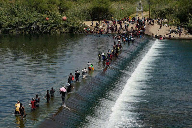 Haitian migrants use a dam to cross into the United States from Mexico in Del Rio, Texas.  - Copyright 2021 The Associated Press. All rights reserved