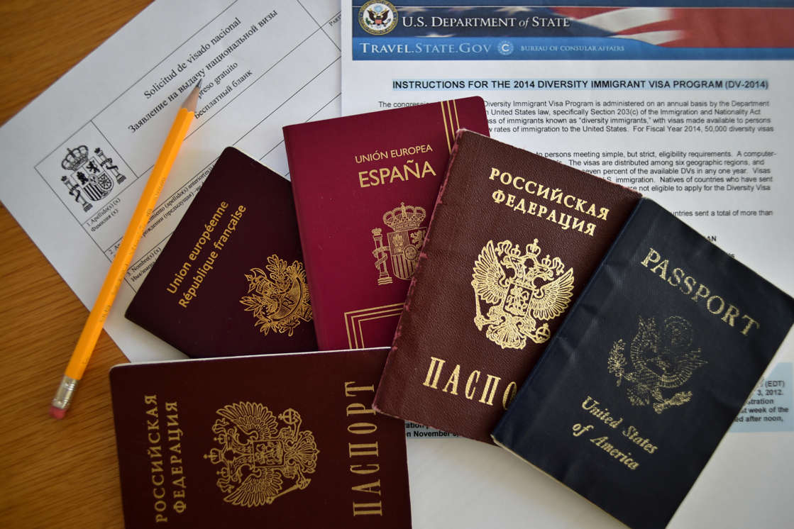 More than 20,000 winners of the U.S. visa lottery are suing the government after their applications were never processed. This July 31, 2014, file photo shows Russian, U.S., Spanish and British passports together with visa application forms.