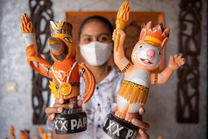 Karyawan menunjukkan suvenir maskot PON Papua Kangpho dan Drawa dipusat oleh-oleh Abepura, Kota Jayapura, Papua, Kamis (30/9/2021). Foto: Nova Wahyudi/ANTARA FOTO