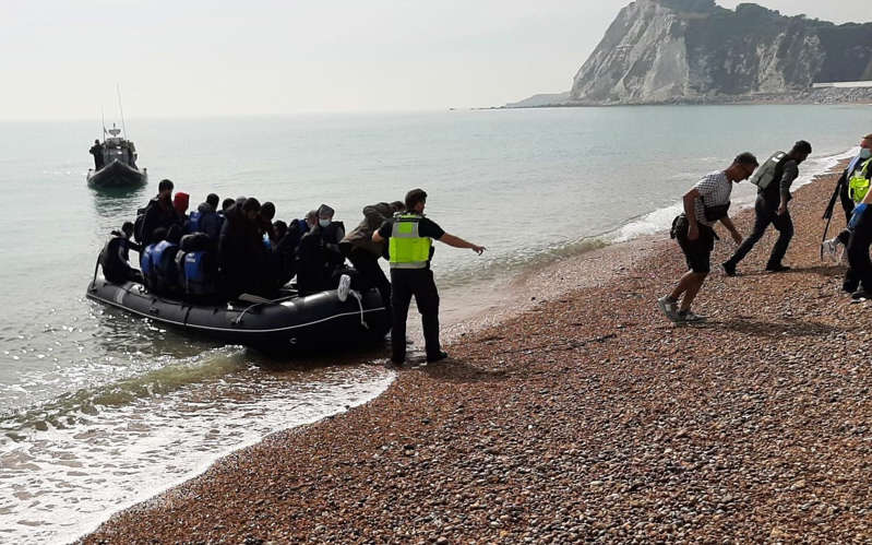 a group of people on a beach: Sunday saw the first small boat crossings for more than two weeks due to bad weather - Henry Bodkin