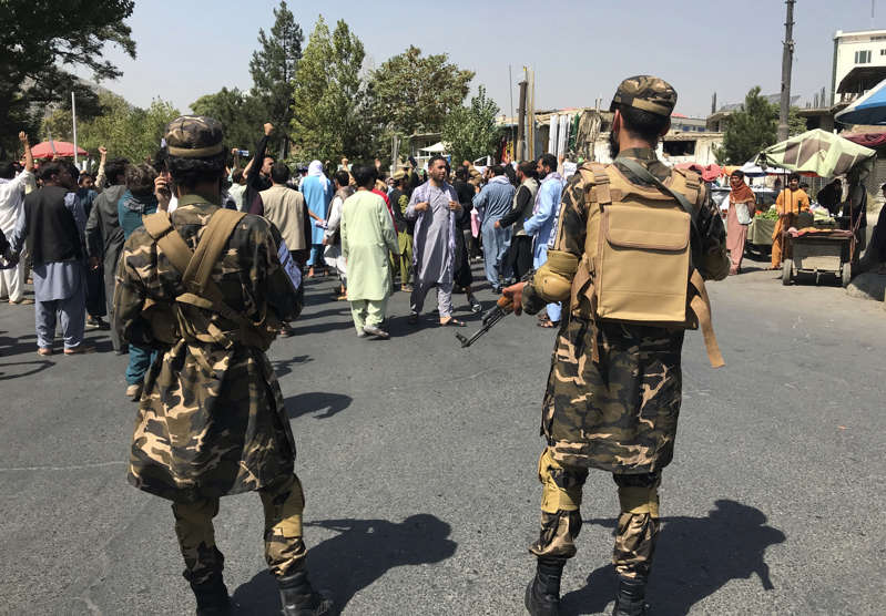 a group of people in military uniform standing in front of a crowd: Taliban soldiers stand by as Afghans shout slogans during an anti-Pakistan demonstration, near the Pakistan embassy in Kabul, Afghanistan, Tuesday, Sept. 7, 2021.