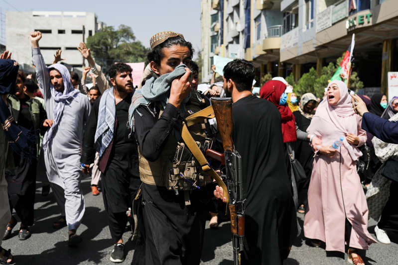 a group of people walking down the street: A Taliban soldier covers his face during an anti-Pakistan protest in Kabul, Afghanistan, September 7, 2021. / Credit: WANA NEWS AGENCY/Reuters