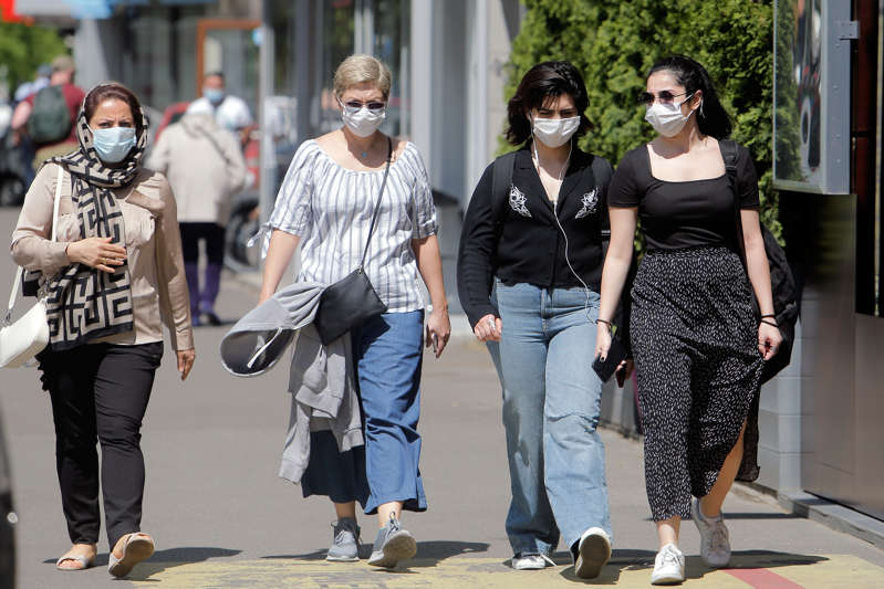People wearing face masks walk on a street in Bucharest, Romania, on May 14, 2021.   (Xinhua/Cristian Cristel via Getty Images)
