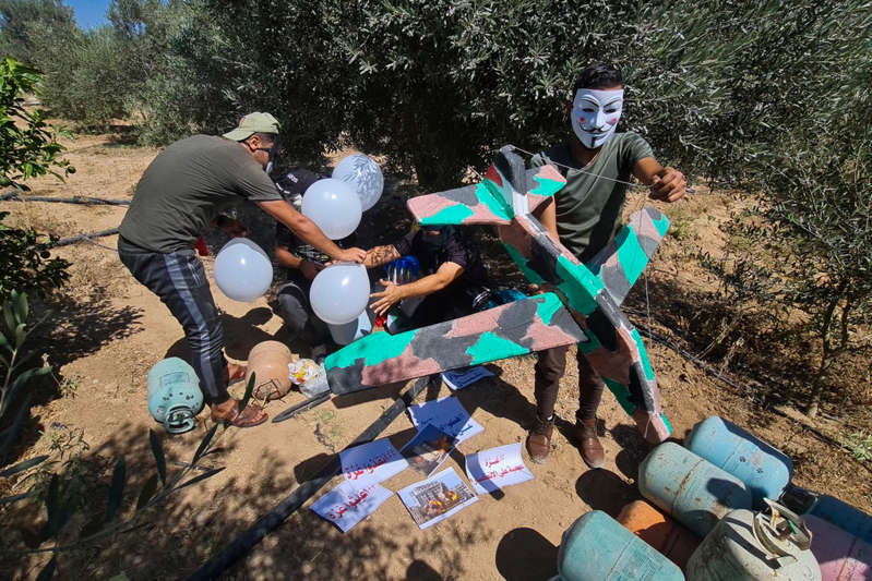 a group of people that are standing in the dirt: Masked Hamas-affiliated operatives launched balloons towards Israel, next to the eastern border of Gaza Strip, prompting Israel to retaliate with air  - AP