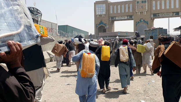 a group of people standing in front of a crowd: People cross Pakistan-Afghanistan border at Friendship Gate in Chaman