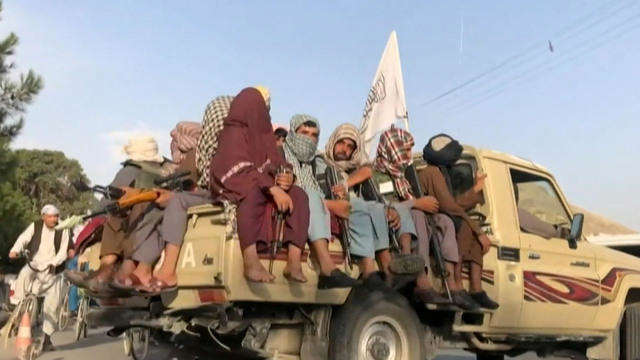 a man riding on the back of a truck: Taliban preventing stranded Americans from le... 02:36