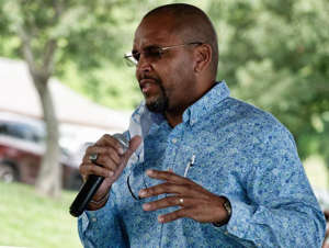 a man talking on a cell phone: U.S. Congress North Carolina 11th District candidate Eric Gash speaks during the first Annual Community Festival Sept. 5 at Sullivan Park.