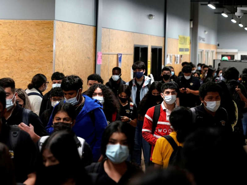 a group of people standing in front of a crowd: Students wear masks while walking to class to prevent the spread of the COVID-19 at Santa Fe South High School in Oklahoma City, Sept. 1, 2021.