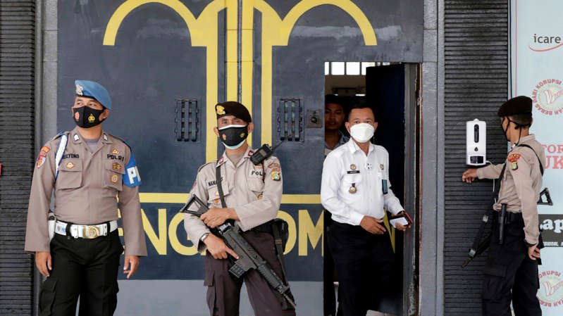 a group of people in uniform standing in front of a building: Police officers at the main entrance gate of Tangerang prison