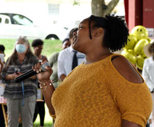 """a person holding a wine glass: YaShara Lynch sings The National Black Anthem, """"Lift Every Voice and Sing,"""" at the first Annual Community Festival Sept. 5 at Sullivan Park."""