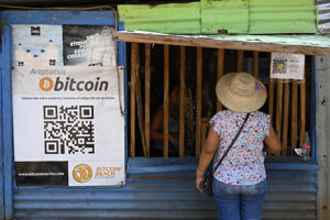 a little girl standing in front of a building: A woman buys in a store that accepts bitcoins in El Zonte, La Libertad, El Salvador on September 4, 2021. / Credit: MARVIN RECINOS/AFP via Getty Images
