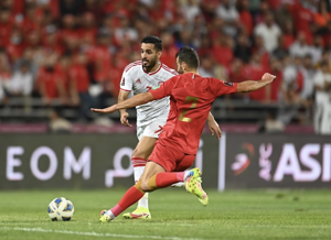 Ali Mabkhout holding a football ball in front of a crowd: World Cup qualifiers: UAE striker Ali Mabkhout equals Pele's record in 1-1 draw with Syria