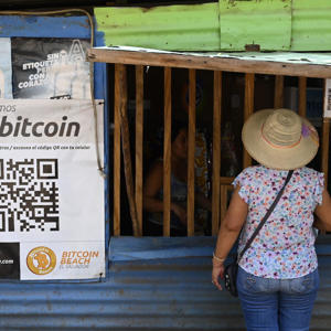 a little girl standing in front of a sign: EL SALVADOR-ECONOMY-CRYPTOCURRENCY-BITCOIN