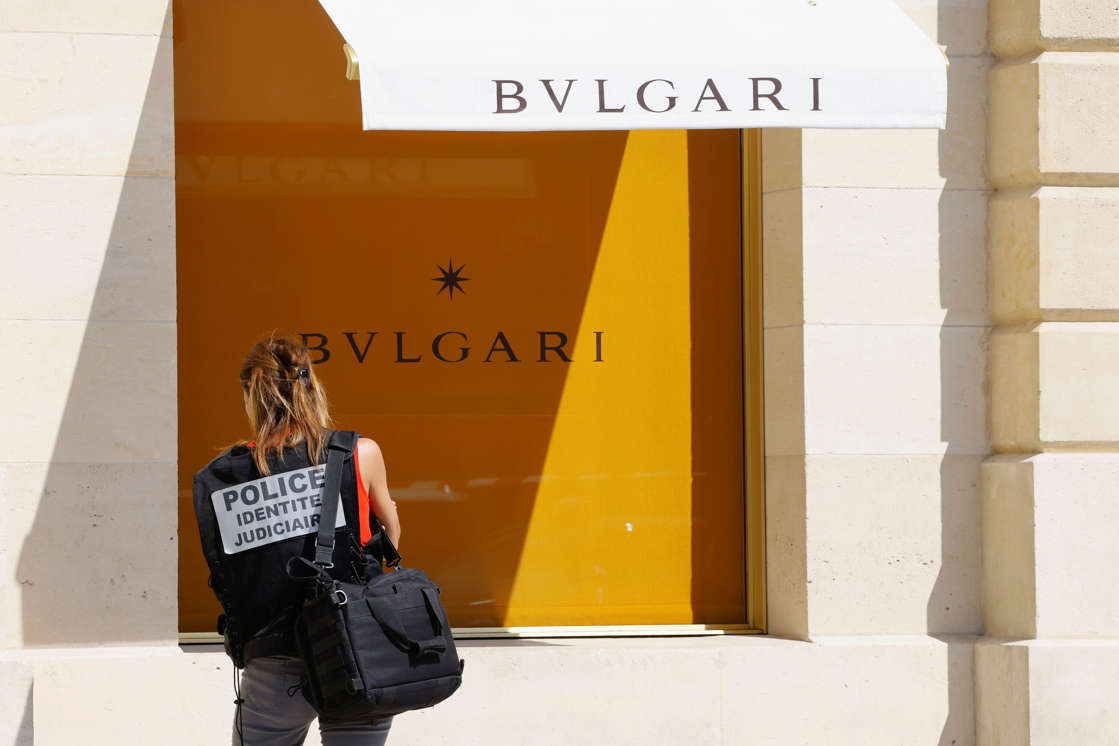 a person holding a sign: French police stand in front of the Bulgari jewelry store following a robbery at Place Vendome in Paris on Tuesday.