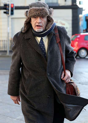Ian Bailey wearing a suit and tie walking down the street: Before giving his theory, Mr Bailey said he was sorry to see Mr Baudy-Vignaud going through the pain of his mum's death, but Mr Bailey maintained that he wasn't involved. Pic: Collins Courts