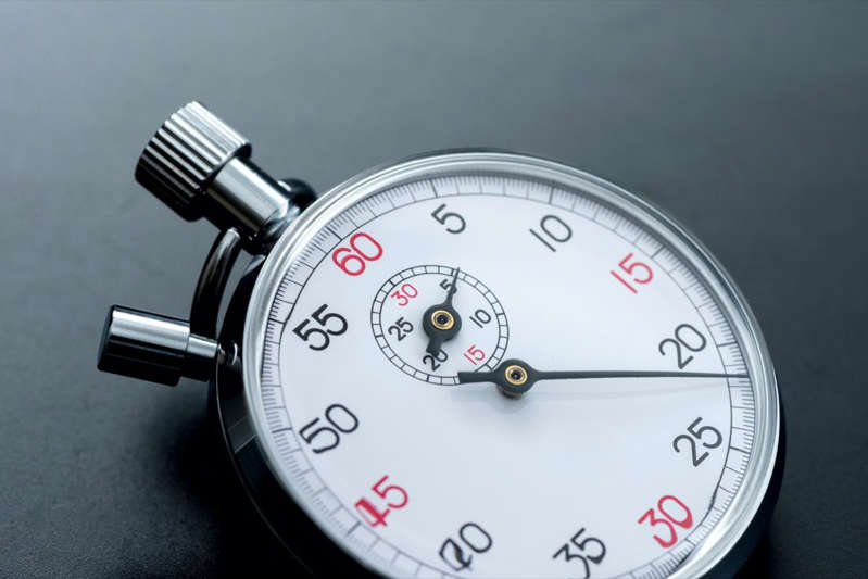 a clock on a table: Analogue metal stopwatch close-up on the black background.