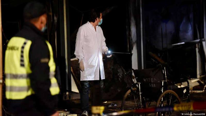 a man standing in front of a store: Injured patients and medical staff were raced to hospitals in the capital Skopje