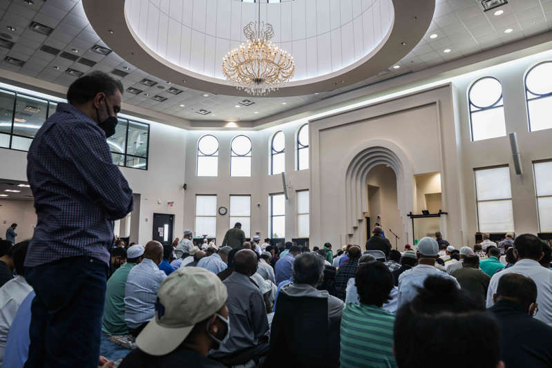 a group of people standing in front of a crowd: A group of Muslim men gather at the mosque main prayer hall to celebrate Friday afternoon prayer and lecture at the East Plano Islamic Center on August 27, 2021.
