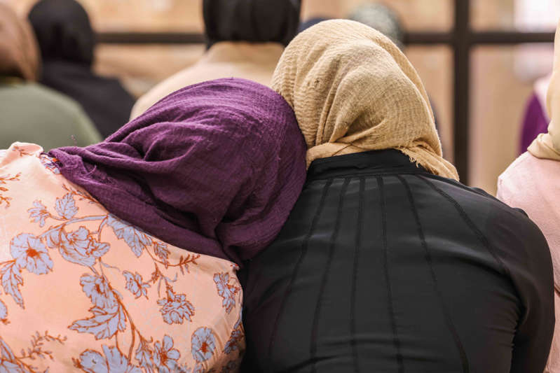 a person sitting on a couch: A group of Muslim women gather on the second floor of the mosque to celebrate Friday afternoon prayer and lecture at the East Plano Islamic Center on August 27, 2021.