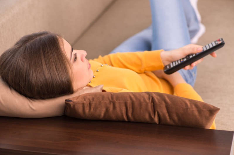 a girl sitting on a couch: woman lying on sofa and watching tv.