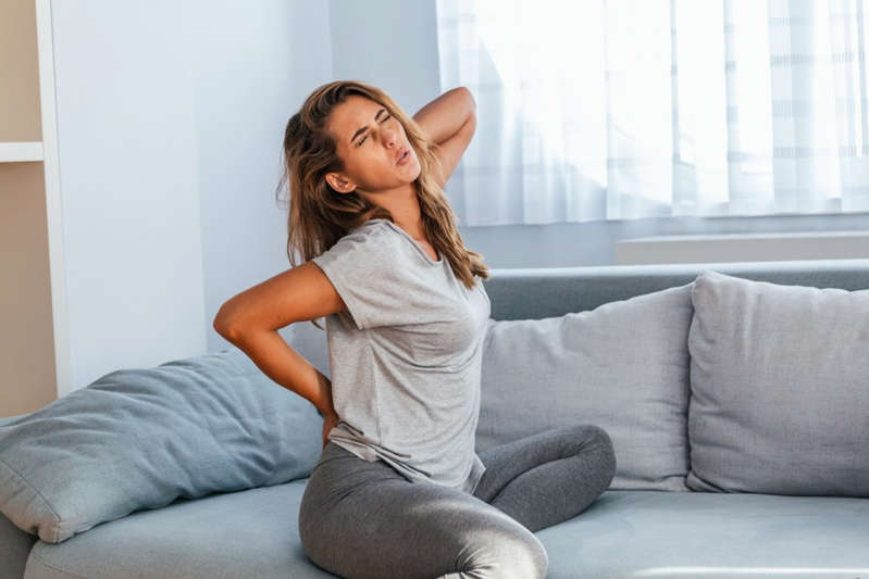 a woman sitting on a sofa: Woman suffering from backache at home