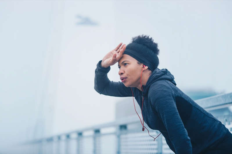 a person jumping in the air: A woman taking a break from a running exercise in an outdoor urban environment.