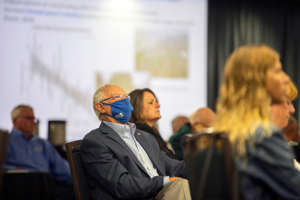 a group of people looking at a phone: Attendees listen to panelists speak at the 2021 Real Estate Symposium on Wednesday, Sept. 8, 2021, at FGCU.
