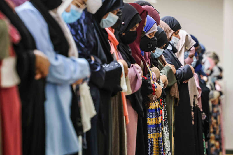 a group of people wearing costumes: A group of Muslim women gather on the second floor of the mosque to celebrate Friday afternoon prayer and lecture at the East Plano Islamic Center on August 27, 2021.