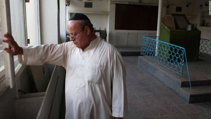 a man standing in a room: Zebulon Simentov, the last known Jewish person living in Afghanistan, closes the window to the synagogue he cares for in his Kabul home on August, 29, 2009.