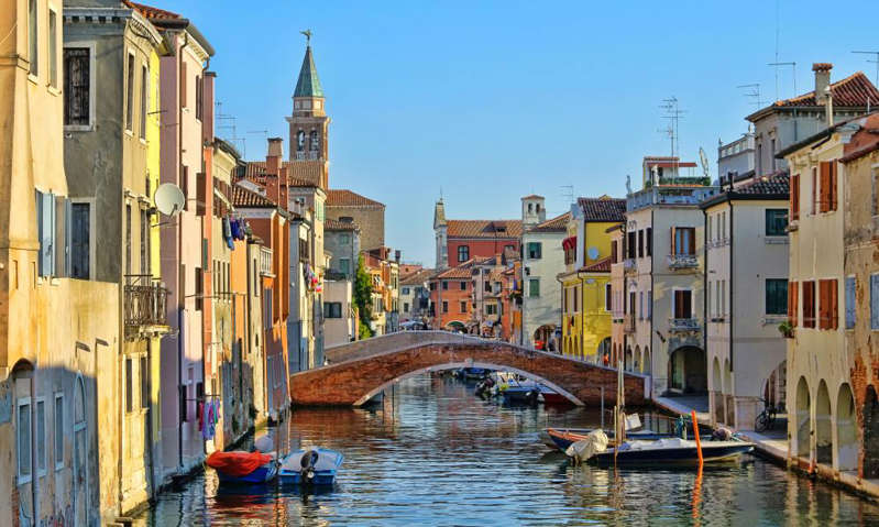 a small boat in a body of water with a city in the background: Great water view of Chioggia with vintage cabins and bridgeChioggia, little Venice in Italy