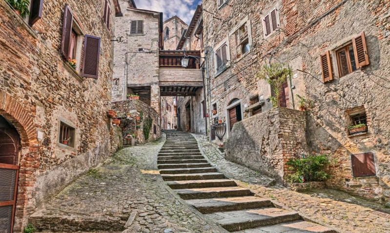 a stone building that has a sign on a brick wall: alley in the medieval village Anghiari, Arezzo, Tuscany