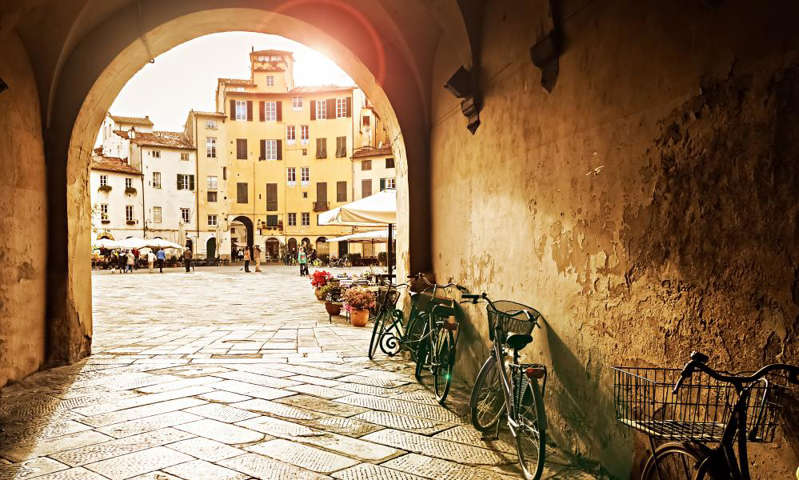 a chair sitting in front of a stone building: Lucca