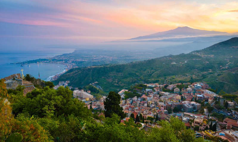 a view of a large mountain in the background: Taormina with Mount Etna at sunset. Photograph: Westend61/Getty Images