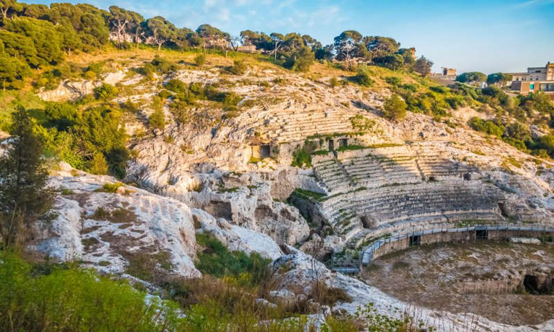 a rocky river with trees on the side of a mountain: The Roman amphitheatre in Cagliari. Photograph: Luis Leamus/Alamy